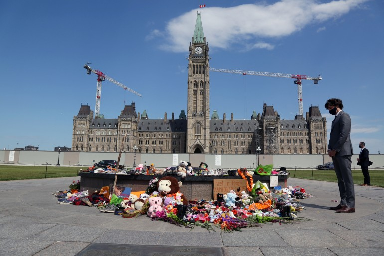 Trudeau visits the makeshift memorial erected in honour of the 215 Indigenous children whose remains were found at a 'residential school' in British Columbia, on Parliament Hill June 1, 2021 in Ottawa [Dave Chan/AFP]