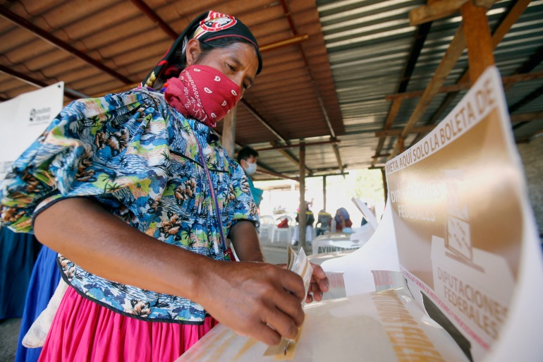 A Wixarika Indigenous woman casts her vote at a polling station during midterm elections in Mezquitic community, Jalisco state, Mexico [Ulises Ruiz/AFP]