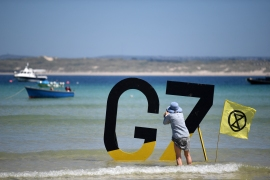 A woman takes a photo of a G7 sign beside an Extinction Rebellion flag in St Ives, Cornwall during the G7 summit [Daniel Leak-Olivas/AFP]