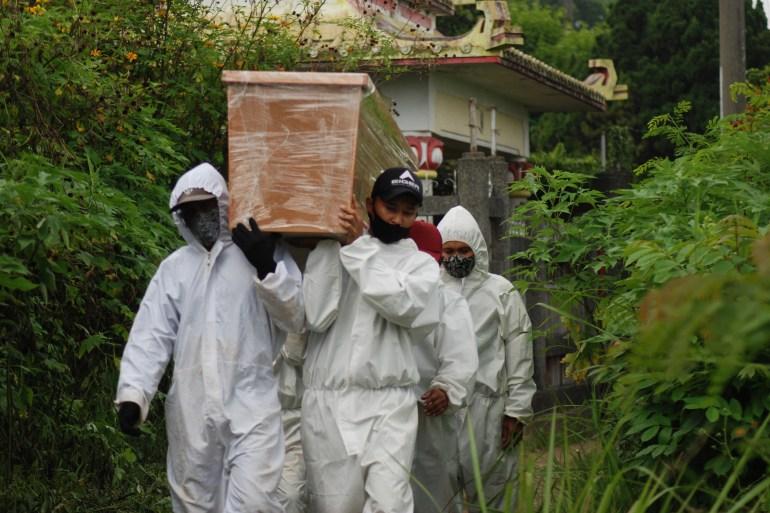 Penggali kubur membawa peti mati untuk dimakamkan di pemakaman orang yang meninggal karena virus corona di Bandung Timur Matahari/AFP
