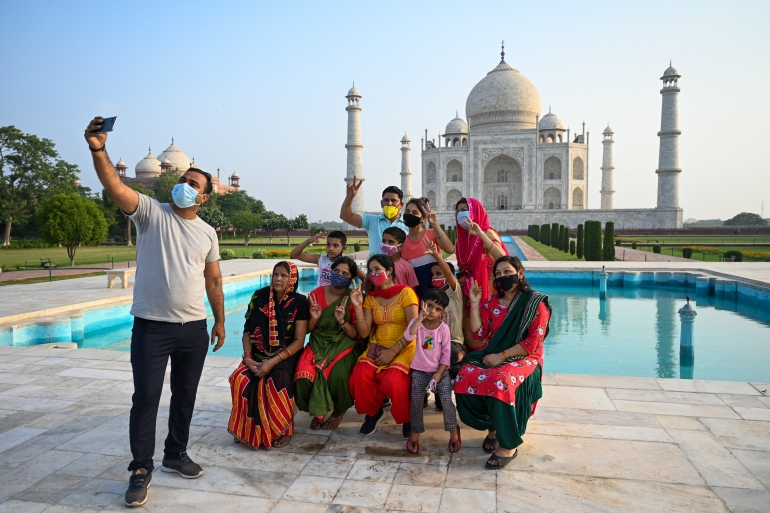 A group of tourists take souvenir photos at the Taj Mahal after it reopened to visitors as authorities eased coronavirus restrictions [Money Sharma/AFP]