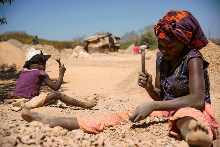 A child and a woman break rocks extracted from a cobalt mine at a copper quarry and cobalt pit in Lubumbashi, DRC [File: AFP/Junior Kannah]