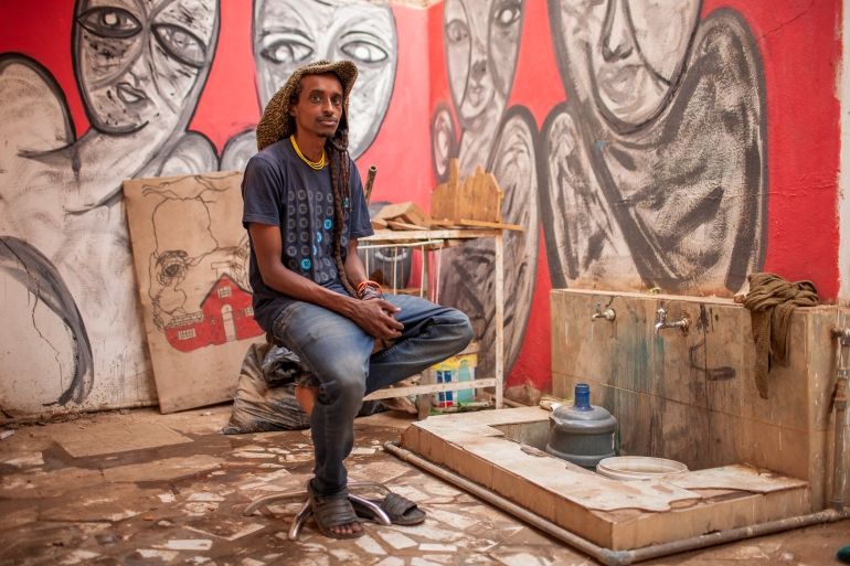 Man sitting on stool in painting area