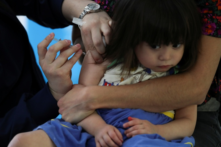 A child receives a vaccine as part of a seasonal flu vaccination campaign for children and elderly people, during the coronavirus disease (COVID-19) pandemic, in Santiago, Chile on April 13 [Ivan Alvarado/Reuters]