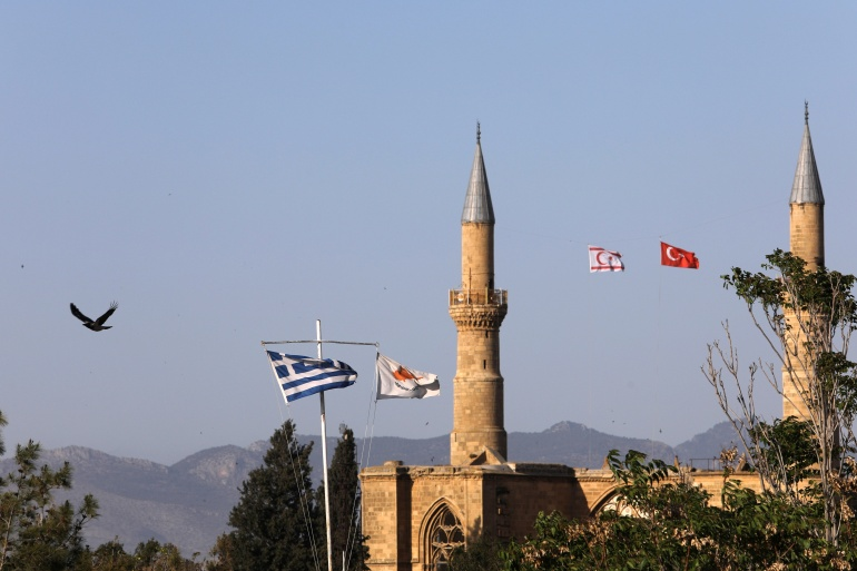 Greek and Cypriot flags along with Turkish and Turkish Cypriot ones are seen near the UN controlled buffer zone in Nicosia, Cyprus April 27, 2021 [Yiannis Kourtoglou/Reuters]