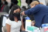 A woman receives a COVID-19 vaccine at Jordan Downs in Los Angeles, California on March 10, 2021 [File: Lucy Nicholson/Reuters]