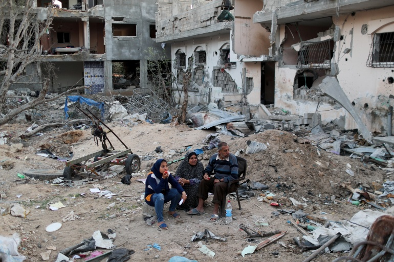 Palestinians sit near houses destroyed by Israeli bombardment, in the northern Gaza Strip June 1, 2021 [Mohammed Salem/Reuters]