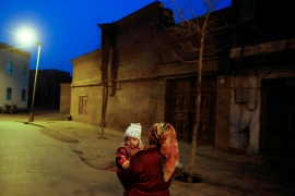 A woman carries a child at night in the old town of Kashgar, Xinjiang Uighur Autonomous Region, China, March 23, 2017 [File: Thomas Peter/ Reuters]