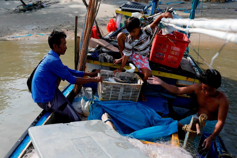 Apriadi Anwar, 45, seorang nelayan setempat, putranya Avanza, 12, dan temannya, mengumpulkan hasil tangkapan mereka saat mereka kembali dari memancing, di desa Batu Perahu, di Toboali, di pantai selatan pulau Bangka  Willy Kurniawan/Reuters