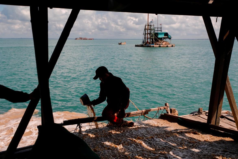 Seorang penambang timah artisanal menggunakan bak plastik untuk memeriksa pasir bijih timah saat mengerjakan ponton di lepas pantai Toboali  Willy Kurniawan/Reuters