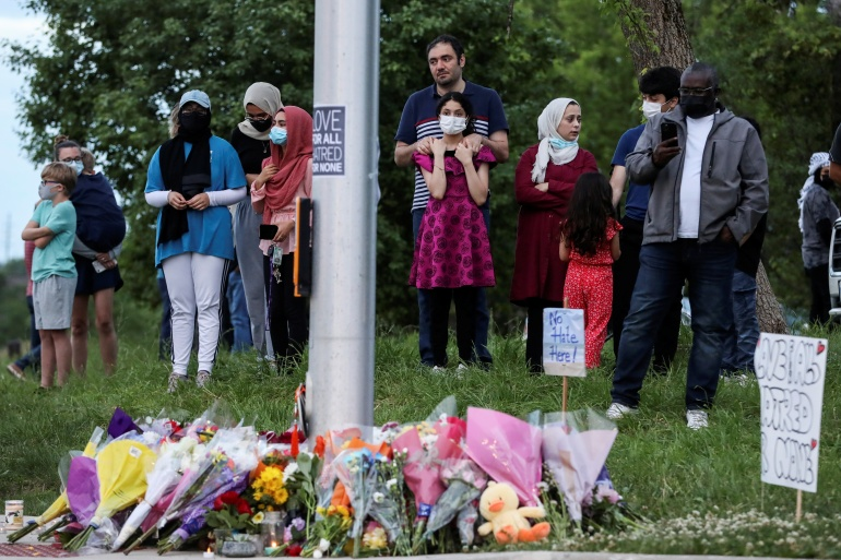 People gather at a makeshift memorial at the scene where a man driving a pick-up truck ran over a Muslim family in what police say was a hate crime [Carlos Osorio/Reuters]