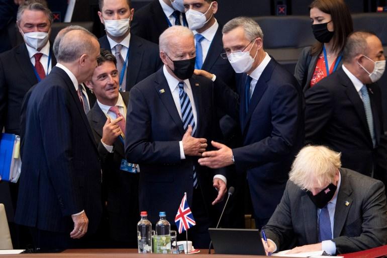Turkey's President Tayyip Erdogan, US President Joe Biden and NATO Secretary General Jens Stoltenberg talk as Britain's Prime Minister Boris Johnson sits before a plenary session at a NATO summit in Brussels, Belgium [Brendan Smialowski/Pool via Reuters]