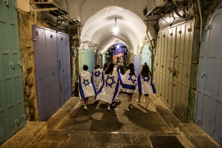 Israeli women cover themselves with Israeli national flags as they walk inside Jerusalem's Old City June 15, 2021. [Ronen Zvulun/Reuters]