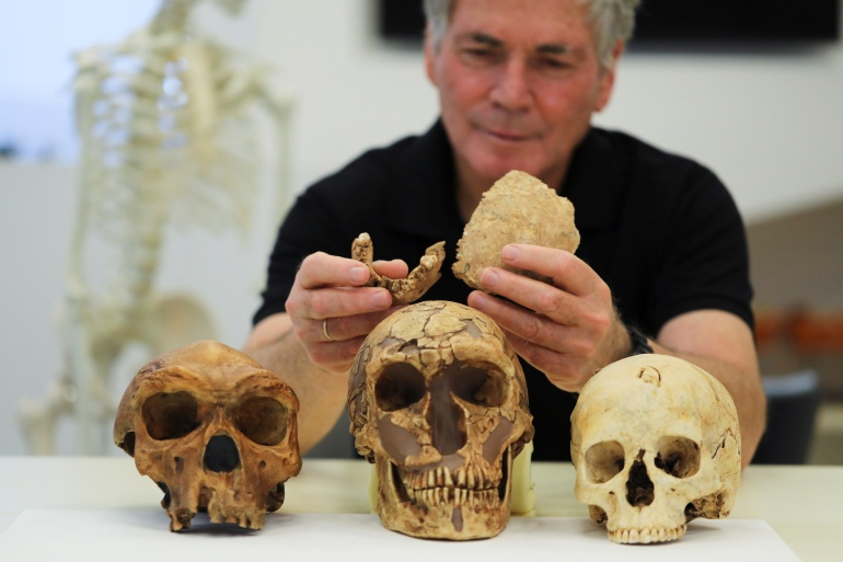 An Israeli scientist holds two pieces of fossilised bone of a previously unknown kind of early human [Ammar Awad/Reuters]