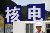 A security guard stands in front of signs displaying the Chinese characters reading 'nuclear power' at the China Guangdong Nuclear Power Group Co plant in Taishan, Guangdong Province, China [File: Qilai Shen/Bloomberg]