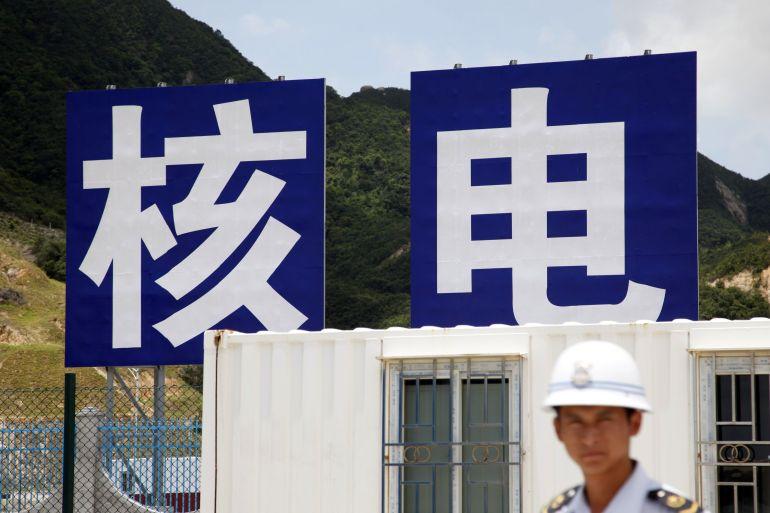 Seorang penjaga keamanan berdiri di depan tandatanda yang menampilkan karakter China membaca 'tenaga nuklir' di pembangkit listrik China Guangdong Nuclear Power Group Co di Taishan, Provinsi Guangdong, China File Qilai Shen/Bloomberg