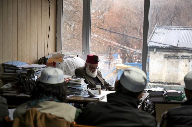 Eighty-one-year old Sufi mystic and poet Haidari Wujodi sits at his desk in Kabul Public Library [Lynzy Billing/Al Jazeera]
