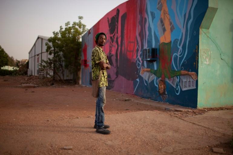 man standing in a area of murals