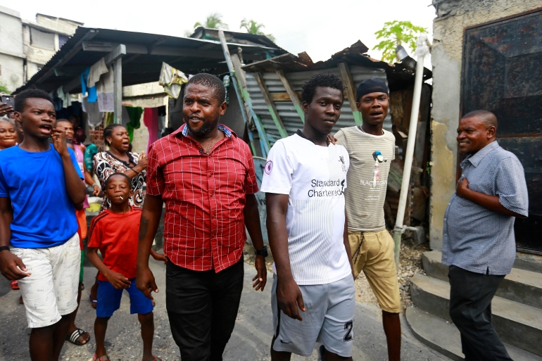 Jimmy Cherizier, known as Barbecue, walks as residents chant, 'Barbecue for life,' in his neighbourhood in Lower Delmas, a district of Port-au-Prince, Haiti in May 2019 [File: Dieu Nalio Chery/AP Photo]