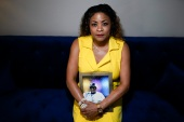Daphne Bolton poses for a portrait holding a photograph of her brother Johnny Lorenzo Bolton, a Black man was to death by a Cobb County Sheriff's Office SWAT team member serving a search warrant last December [File: Chris Carlson/AP Photo]