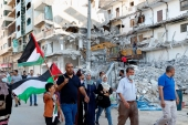Protesters in Gaza City wave Palestinian flags while marching past a building destroyed by an Israeli air raid last month [Adel Hana/AP Photo]