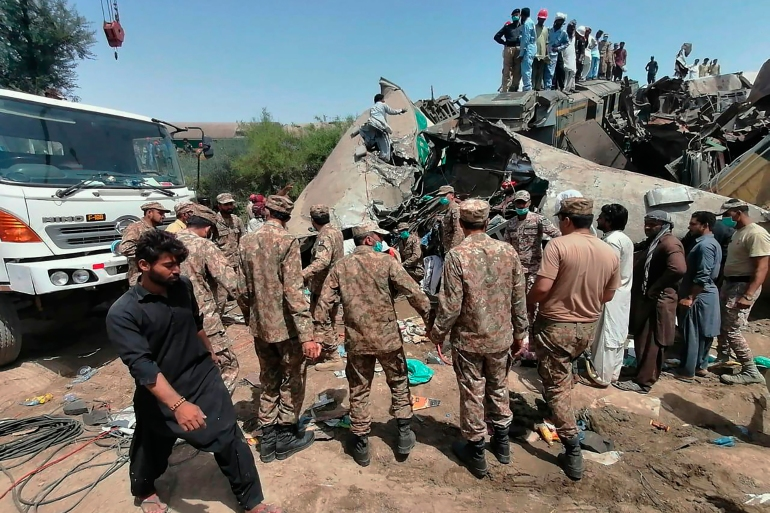In this photo released by Pakistan's army media wing Inter Services Public Relations, troops and rescue workers gather at the site of collision in southern Pakistan [Inter Services Public Relations via AP]