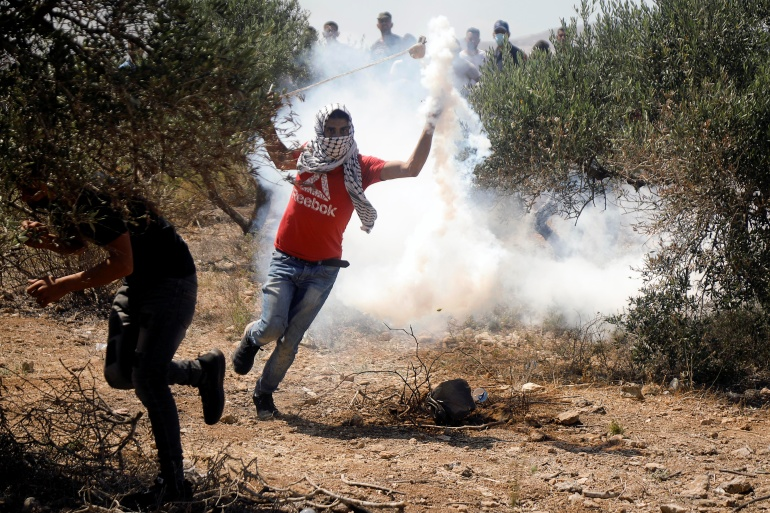 A Palestinian demonstrator throws back a tear gas canister fired by Israeli forces during a protest against Israeli settlements in Beita in the Israeli-occupied West Bank [Raneen Sawafta/Reuters]