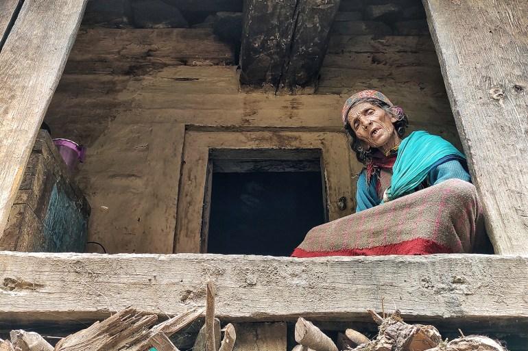 Malana resident Bhudhi Devi chanting the name of the local deity at her house [Srishti Jaswal/Al Jazeera]