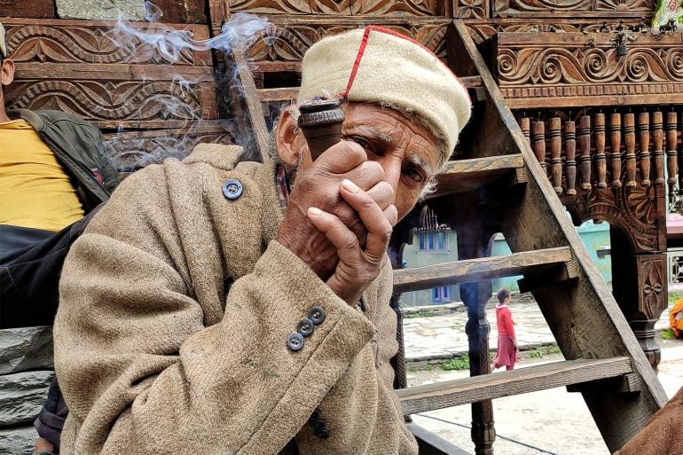 Chetram caretaker of the Jamadagni Rishi deity s temple while smoking his chillum in Malana. Credits Srishti Jaswal for Al Jazeera 1