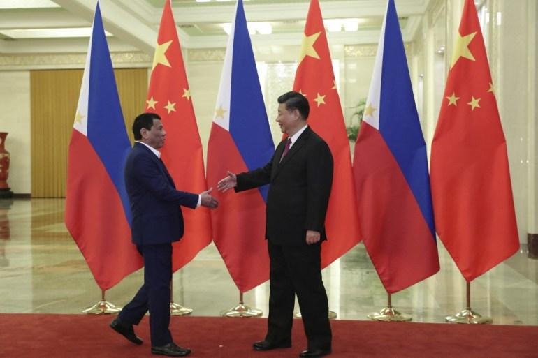 Chinese President Xi Jinping greets his Philippine counterpart Rodrigo Duterte during the latter's visit to Beijing in 2019 [File: Kenzaburo Fukuhara/AFP]