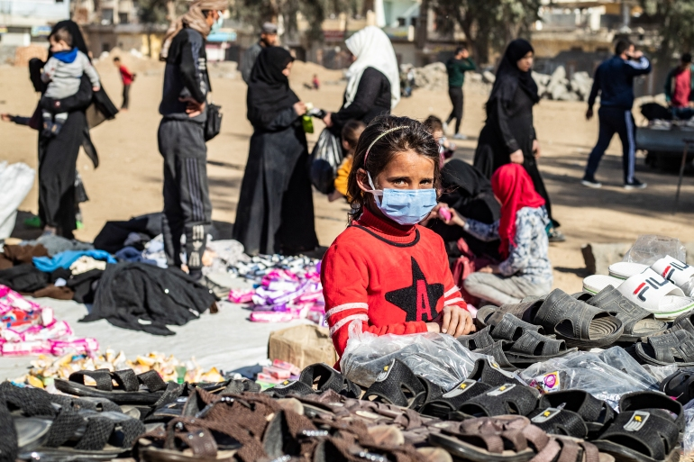 A girl wearing a protective mask amid the COVID-19 pandemic sells slippers at an open-air market in the city of Raqqa in Syria [File: Delil Souleimani/AFP]
