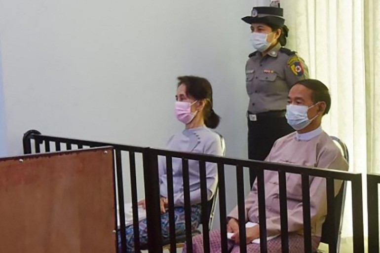 A handout photo released by Myanmar's military government shows detained civilian leader Aung San Suu Kyi (left) and detained president Win Myint (right) during their first court appearance in the capital, Naypyidaw, last May [Handout photo via AFP]