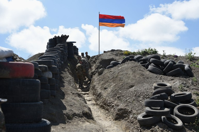 Soldiers walk in a trench at a border checkpoint between Armenia and Azerbaijan near the village of Sotk [File: Karen Minasyan/AFP]