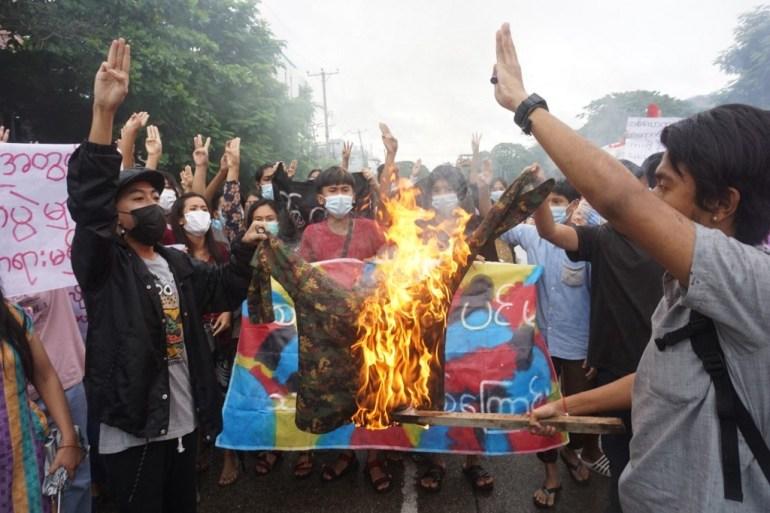 Para pengunjuk rasa membakar seragam militer saat mereka mengambil bagian dalam demonstrasi flash mob menentang kudeta militer di Yangon pada hari Kamis  bulan kelima sejak kudeta Stringer/AFP