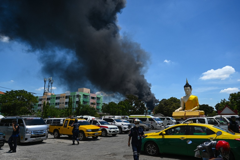 A Buddha statue is seen as smoke billows from an explosion and fire at a plastics factory in Bangkok on July 5, 2021 [Lillian Suwanrumpha/ AFP]