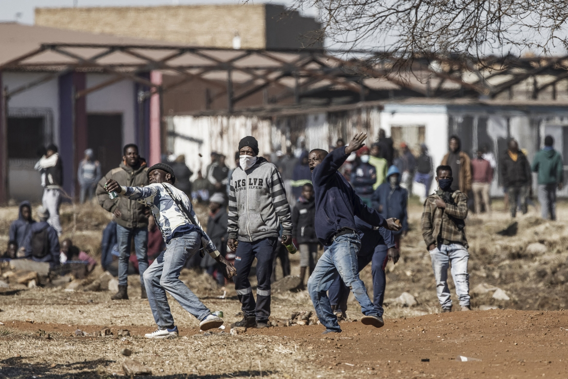 People throw rocks as they confront police officers at the entrance of a partially looted mall in Vosloorus. [Marco Longari/AFP]