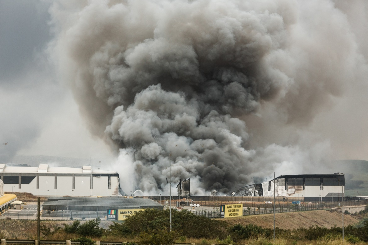 Smoke rises from a Makro building set on fire overnight in Umhlanga, north of Durban. [Rajesh Jantilal/AFP]