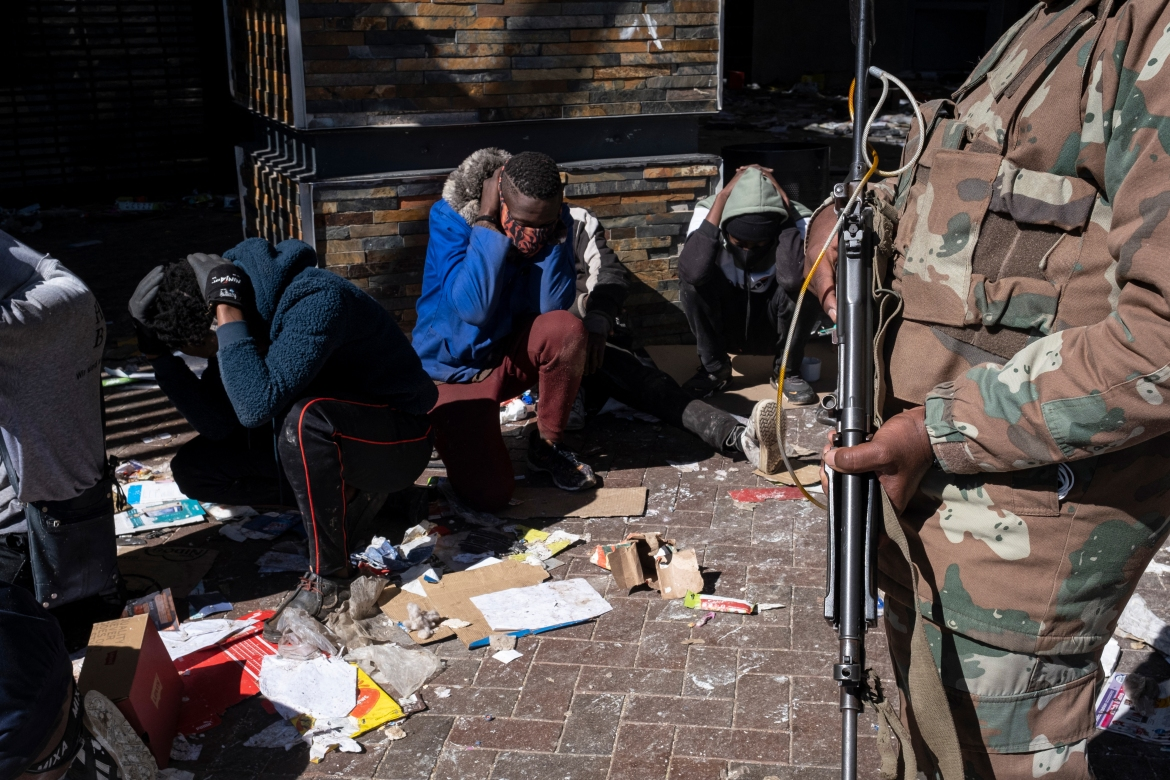 A South African National Defence Force (SANDF) soldier detains suspected looters at the Jabulani mall in Soweto on the outskirts of Johannesburg. [Emmanuel Croset/AFP]