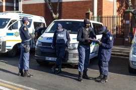 Members of the South African Police Services (SAPS) stand guard guard outside the High Court, where the corruption trial of South African ex-president Jacob Zuma resumed briefly before again being adjourned [Guillem Sartorio/AFP]