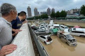 People look out at cars sitting in floodwaters after heavy rains hit the city of Zhengzhou in China's central Henan province [AFP]