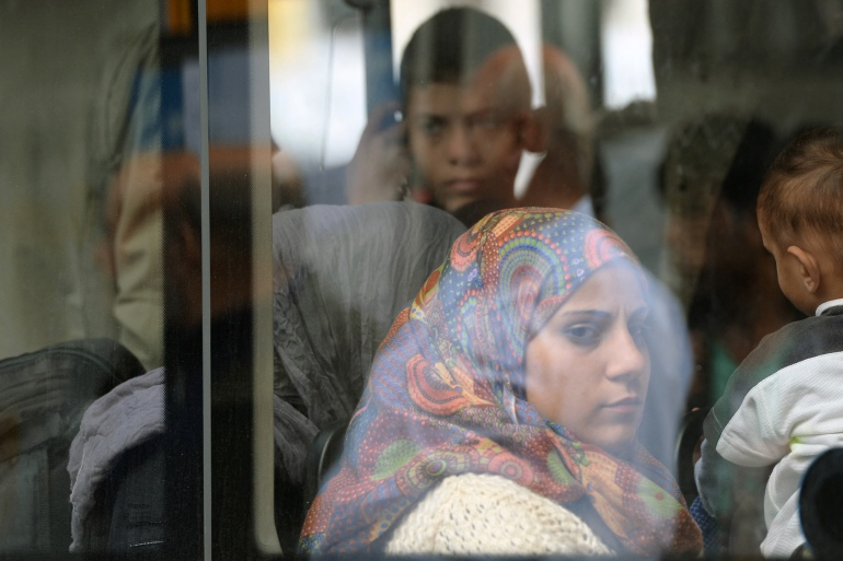 Refugees sit in a bus after they arrive at the main railway station in Munich, southern Germany, September 7, 2015 [File: Christof Stache/AFP]