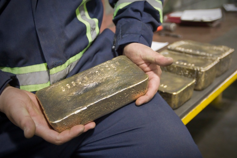 A worker holds a polished gold alloy bar in a workshop at Kumtor gold mine extraction factory in the Tien Shan mountains, some 350km (218 miles) southeast of the capital Bishkek near the Chinese border March 14 [File: Shamil Zhumatov/Reuters]