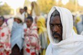 A man stands in line to receive food donations, at the Tsehaye primary school, which was turned into a temporary shelter for people displaced by conflict, in the town of Shire, Tigray region, Ethiopia, March 15, 2021 (Reuters)