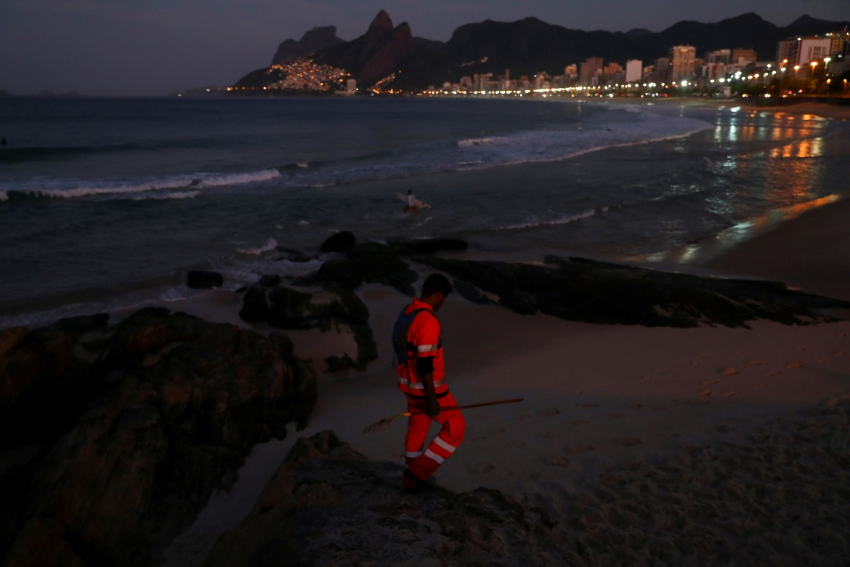 Luther walks along Arpoador Beach during his work shift. [Pilar Olivares/Reuters]