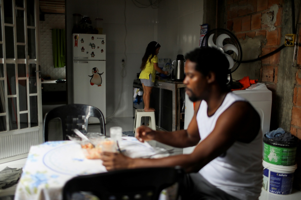 Luther takes part in an online class for his university as he has lunch with his stepdaughter Mirella da Silva, eight, at their home in Belford Roxo. [Pilar Olivares/Reuters]