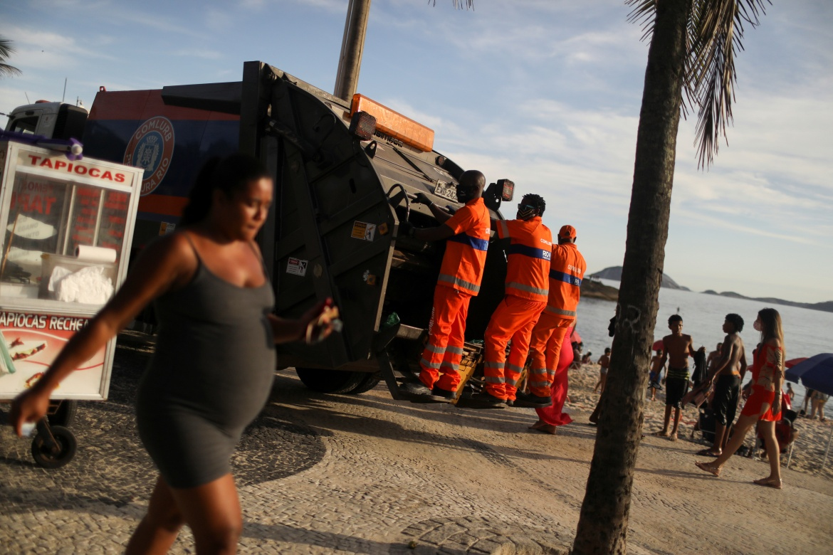 Luther stands on a rubbish truck as he works at Arpoador Beach in Rio de Janeiro. 'When I tell my classmates about my job, they're often shocked,' he said. [Pilar Olivares/Reuters]