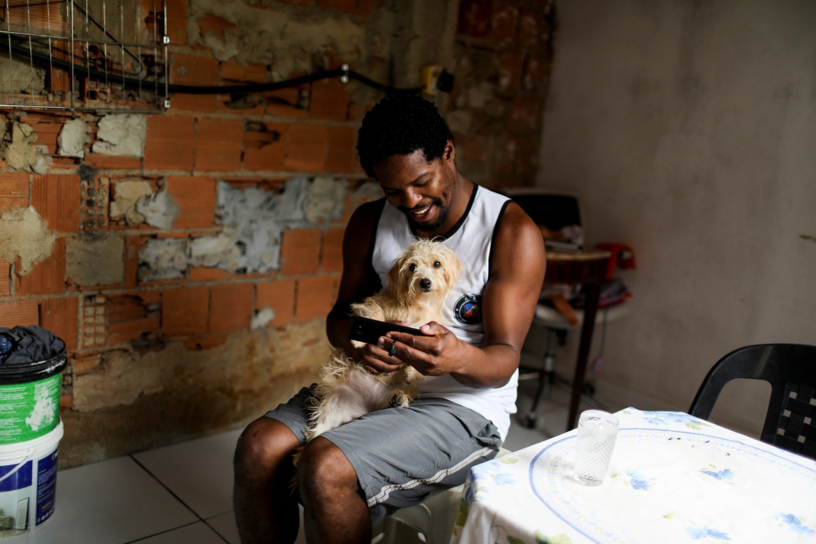 Felipe Luther uses his mobile phone to take part in an online class for his university, as he holds his dog Mel at his home in Belford Roxo, near Rio de Janeiro. [Pilar Olivares/Reuters]
