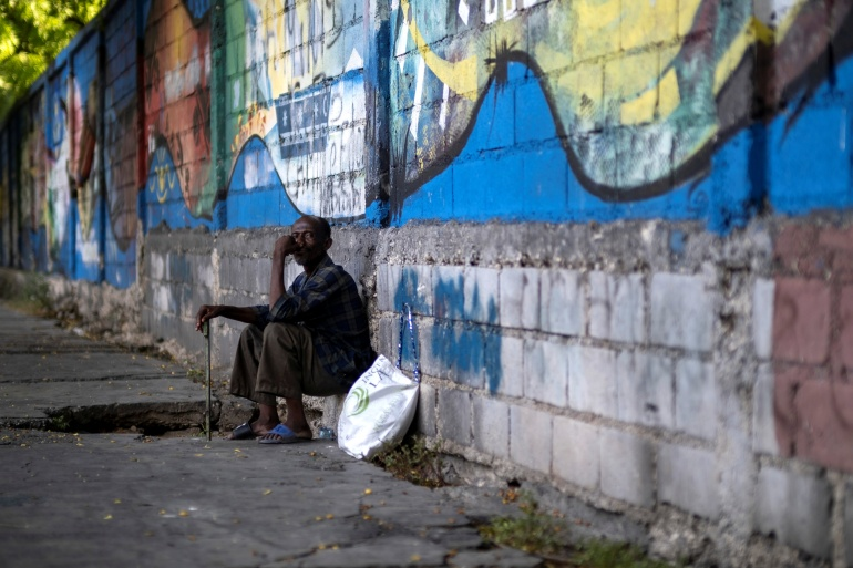 A man sits on a sidewalk in Port-au-Prince following the assassination of President Jovenel Moise, on July 10, 2021 [File: Ricardo Arduengo/Reuters]