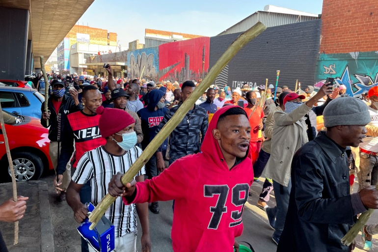 Stick-wielding protesters march through the streets as violence following the jailing of former South African President Jacob Zuma spread to the country's main economic hub in Johannesburg, South Africa, July 11, 2021 [Siphiwe Sibeko/Reuters]