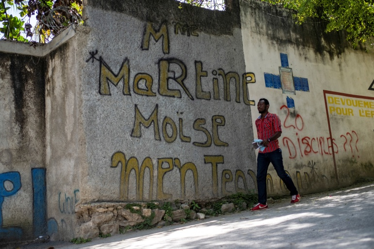 A man walks past graffiti that reads 'Martine Moise' near the house where President Jovenel Moise was assassinated, in Port-au-Prince, Haiti on July 11 [Ricardo Arduengo/Reuters]